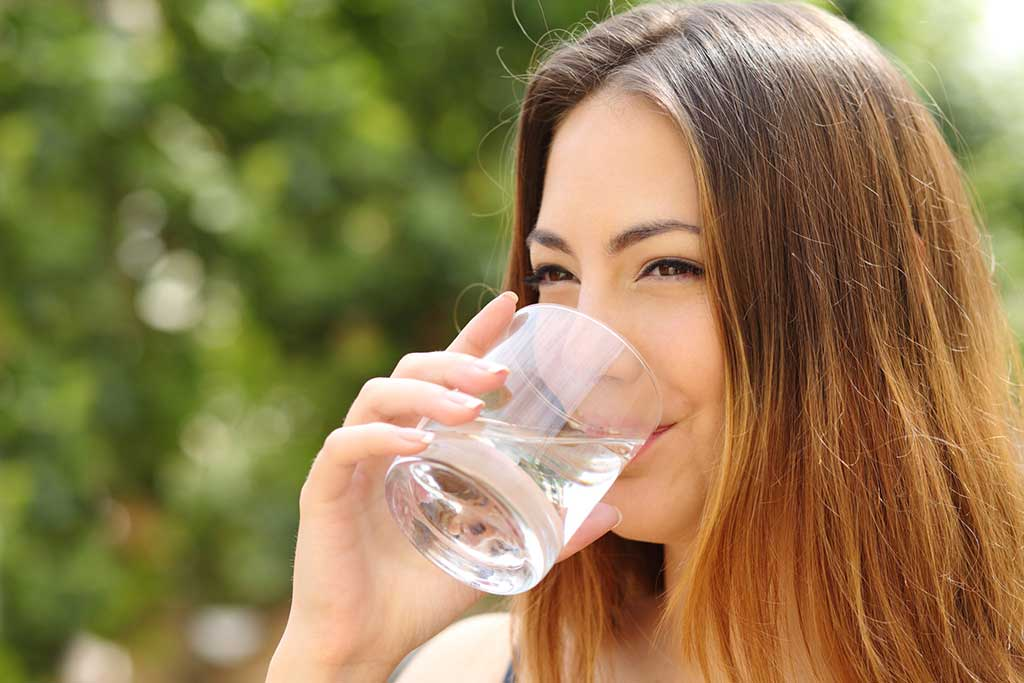 woman drinking clean water from a glass